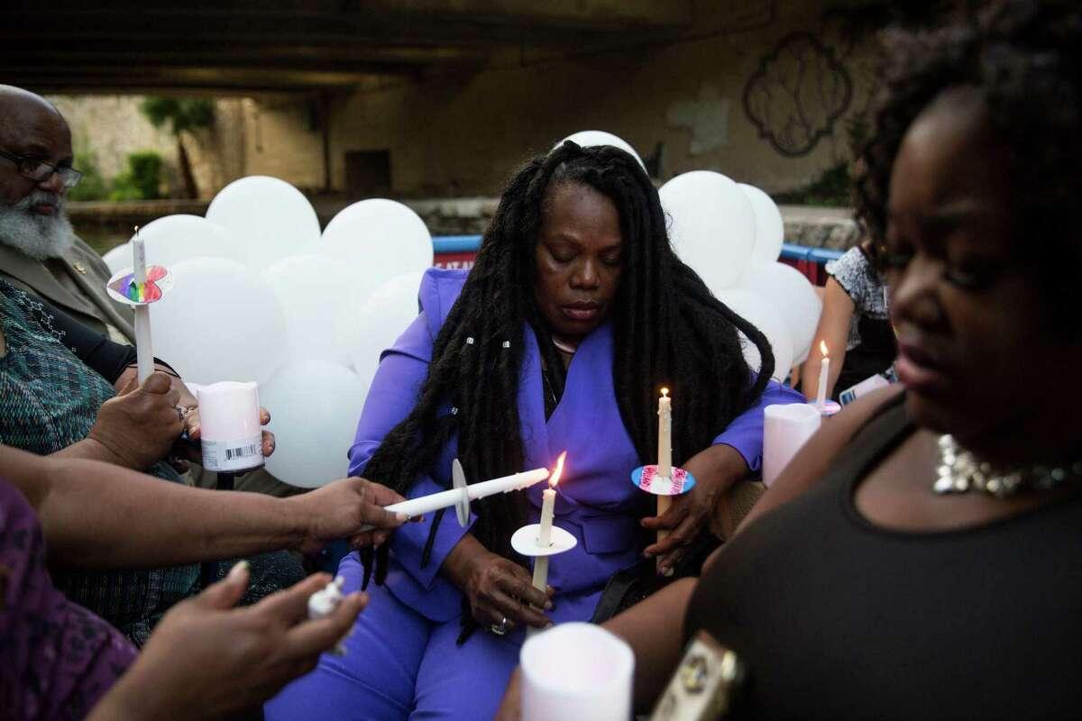 Joann McFadden prays during a vigil for her daughter Kenne McFadden, a trans woman.