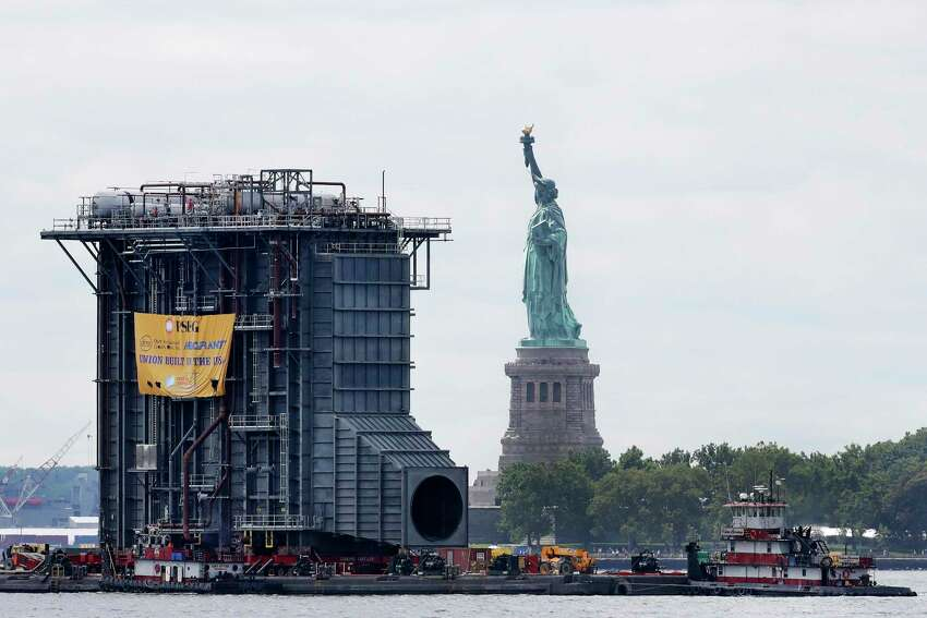 Tugboats guide a barge laden with a $195 million heat-recovery steam generator past the Statue of Liberty, Tuesday, Aug. 8, 2017, in New York. The generator is a component of a new, $600 million power plant being built by PSEG. The equipment was assembled in Coeymans, N.Y. and is destined for the Sewaren 7 power plant in Woodbridge, N.J. (AP Photo/Mark Lennihan) ORG XMIT: NYML102