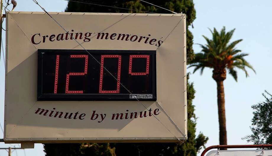 FILE - In this June 20, 2017, file photo, a local temperature sign reads 120-degrees as temperatures climb to near-record highs in Phoenix. As President Donald Trump touts new oil pipelines and pledges to revive the nation's struggling coal mines, federal scientists are warning that burning fossil fuels is already driving a steep increase in the United States of heat waves, droughts and floods. (AP Photo/Ross D. Franklin, File) ORG XMIT: WX117 Photo: Ross D. Franklin / Copyright 2017 The Associated Press. All rights reserved.