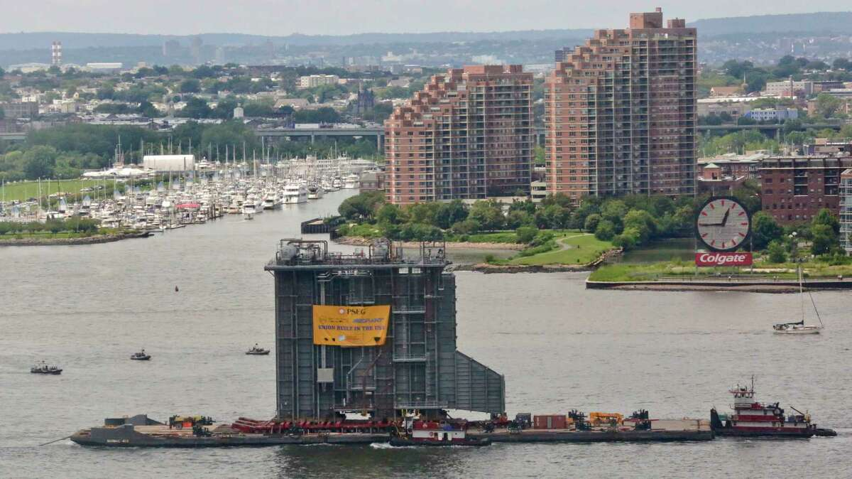 Tug boats guide a barge with a $195 million heat-recovery steam generator along the Hudson River, Tuesday Aug. 8, 2017, in New York. The generator is the component of a new $600 million power plant being built by PSEG. (AP Photo/Bebeto Matthews) ORG XMIT: NYBM104