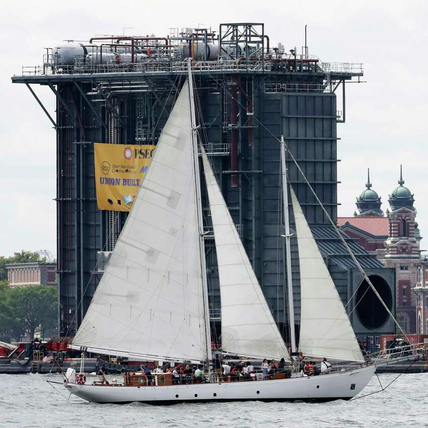 The sailboat Shearwater passes a barge laden with a $195 million heat-recovery steam generator, Tuesday, Aug. 8, 2017, in New York. The 130-foot-(40-meter)-tall generator is a component of a new, $600 million power plant being built by PSEG. The equipment was assembled in Coeymans, N.Y. and is destined for the Sewaren 7 power plant in Woodbridge, N.J. (AP Photo/Mark Lennihan) ORG XMIT: NYML103