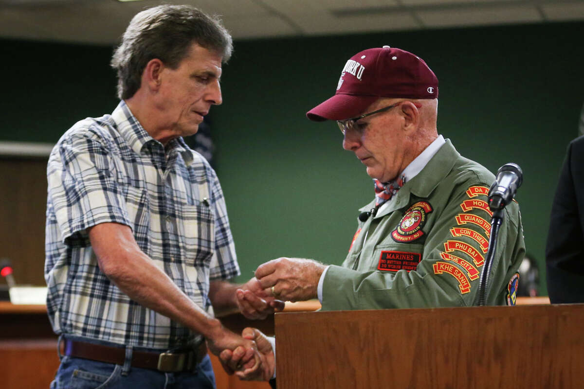Vietnam Veteran Eddie Neas, right, presents the dog tag of Vietnam Veteran Lance Cpl. David Bruce Freed, who was killed in action, to Freed's brother Magnolia resident Brian Dale Freed, left, during a ceremony on Tuesday, Aug. 8, 2017, at Magnolia City Hall.