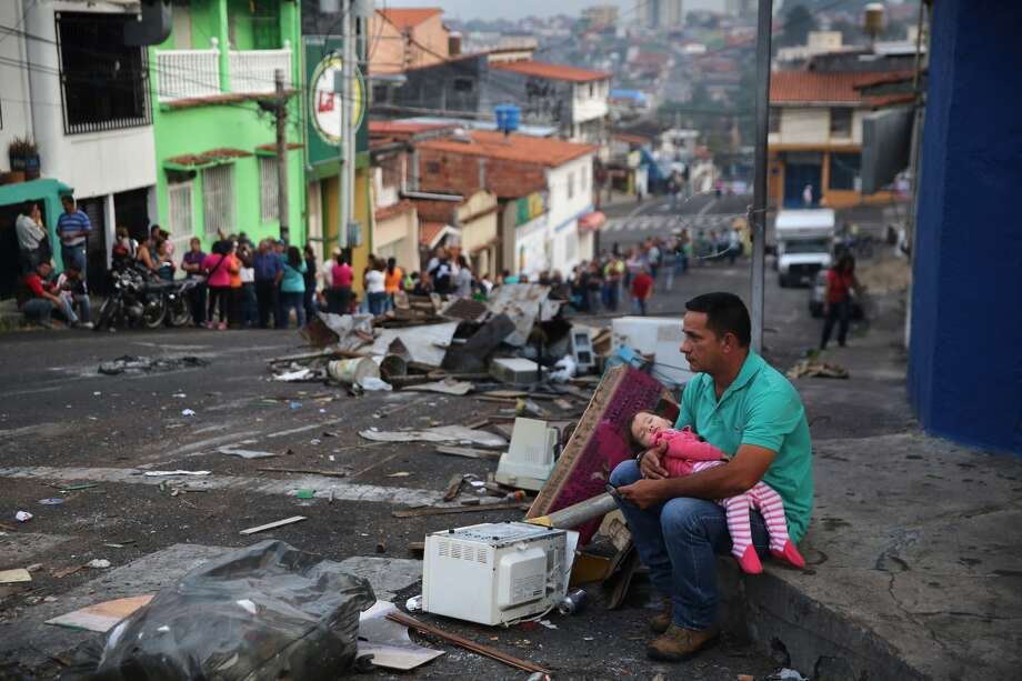 A father and daughter rest while someone holds their place in a long line at a supermarket in San Cristobal, Venezuela. Photo: John Moore / Getty Images