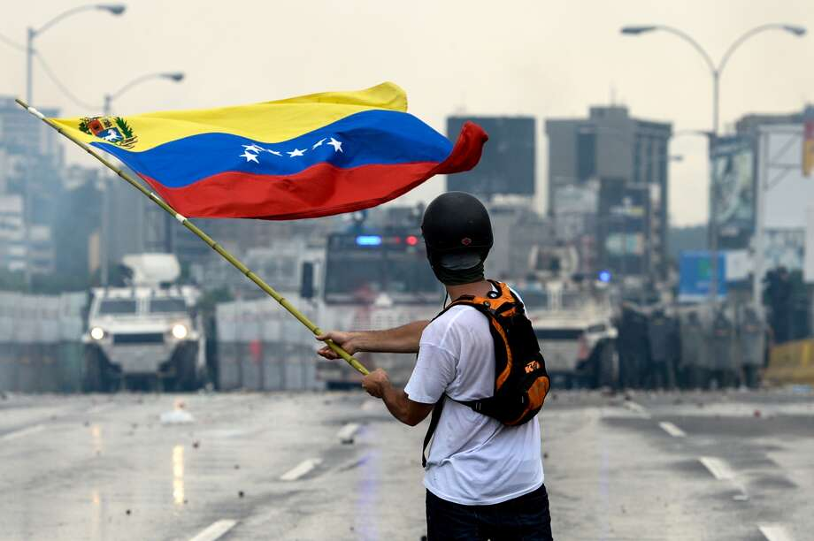 A Venezuelan opposition demonstrator waves a flag at riot police in a