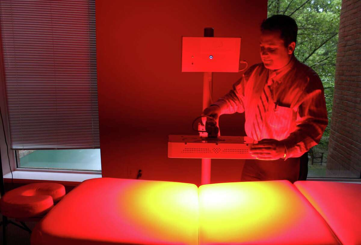 Jason Lord, of New Canaan, demonstrates how the red laser light therapy works at his new center, Laser Body Renewal, at 15 River Road in Wilton Center.