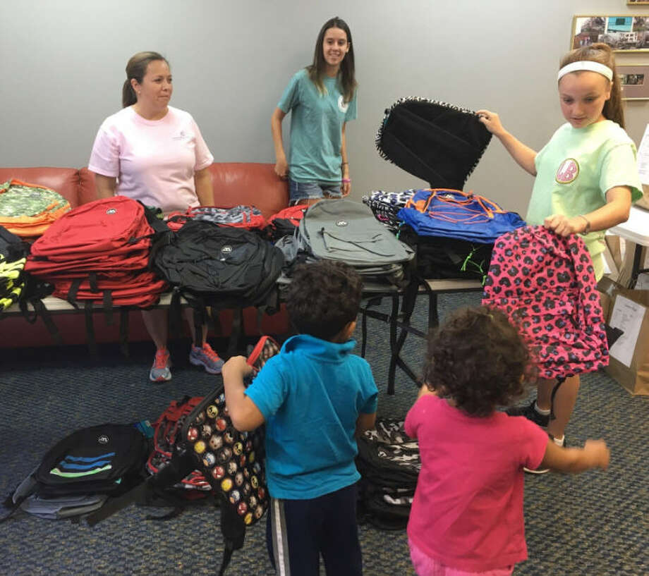 Volunteers at Katy Christian Ministries distributed school supplies Monday. After receiving supplies, schoolchildren picked a backpack from a table of backpacks. Volunteers helping, from left, are: Yvonne Trevino, Caitlin Furley and Lulu Aklestad. Photo: Karen Zurawski