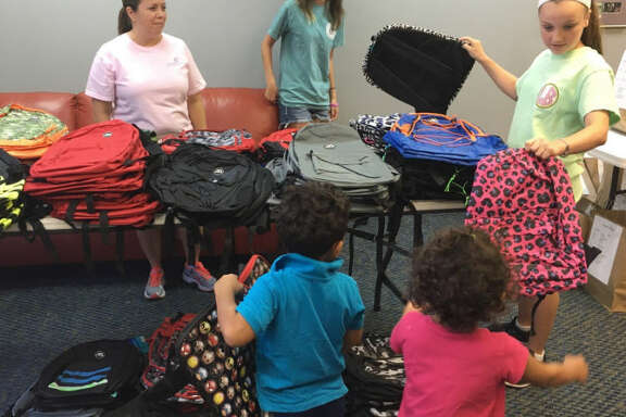 Volunteers at Katy Christian Ministries distributed school supplies Monday. After receiving supplies, schoolchildren picked a backpack from a table of backpacks. Volunteers helping, from left, are: Yvonne Trevino, Caitlin Furley and Lulu Aklestad.