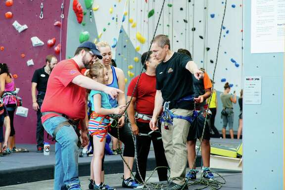 A youth climber receives instruction during the grand opening of Momentum Indoor Climbing Katy. An estimated 1,000 people attended the grand opening.