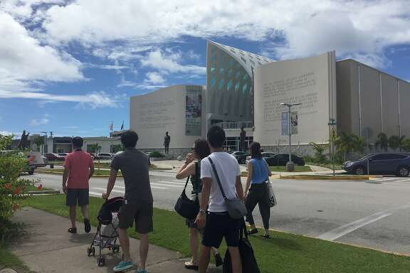 People walk around Hagatna, Guam Wednesday, Aug. 9, 2017. Despite government assurances, residents of the U.S. territory Guam say they�re afraid after being caught in the middle of rising tensions between President Donald Trump and North Korea. (AP Photo/Grace Garces Bordallo)