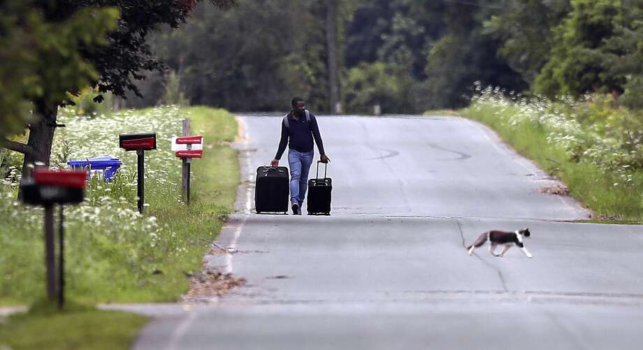 Dulne Brutus of Haiti tows his luggage down Roxham Road in Champlain N.Y. while heading to an unofficial border station across from St.-Bernard-de-Lacolle Quebec