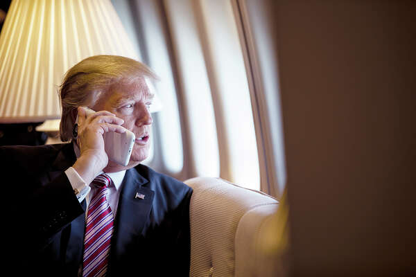 President Donald Trump talks on the phone aboard Air Force One during a flight to Philadelphia, Pennsylvania, to address a joint gathering of House and Senate Republicans, Thursday, January 26, 2017. This was the President's first Trip aboard Air Force One.