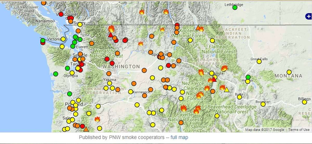 This screenshot shows air quality monitor stations as well as several large fires burning in Washington and beyond. Green is good air, yellow is moderate, orange is unhealthy for sensitive groups and red is unhealthy. A purple dot would mean air quality was hazardous at that point.