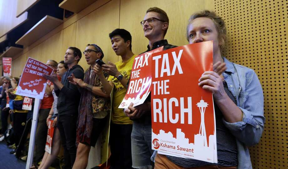 Audience members line a back wall of a room as they look on during public comments at a Seattle City Council meeting where a new city income tax on the wealthy was being considered Monday, July 10, 2017, in Seattle. The council ultimately passed the tax in a 9-0 vote. (AP Photo/Elaine Thompson) Photo: Elaine Thompson/AP