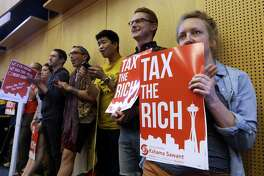 Audience members line a back wall of a room as they look on during public comments at a Seattle City Council meeting where a new city income tax on the wealthy was being considered Monday, July 10, 2017, in Seattle. Seattle's highest earners would become the only Washington state residents to pay an income tax under the proposal that is designed to open a broader discussion about whether the wealthy pay their fair share in this booming city. (AP Photo/Elaine Thompson)