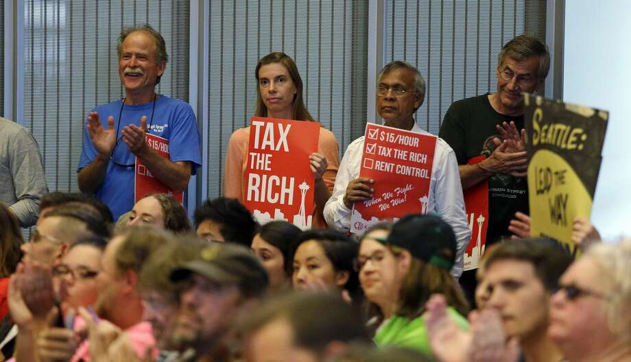 Audience members applaud as they look on during public comments at a Seattle City Council meeting where a new city income tax on the wealthy was being considered Monday, July 10, 2017, in Seattle. Seattle's highest earners would become the only Washington state residents to pay an income tax under the proposal that is designed to open a broader discussion about whether the wealthy pay their fair share in this booming city. (AP Photo/Elaine Thompson) Photo: Elaine Thompson/AP