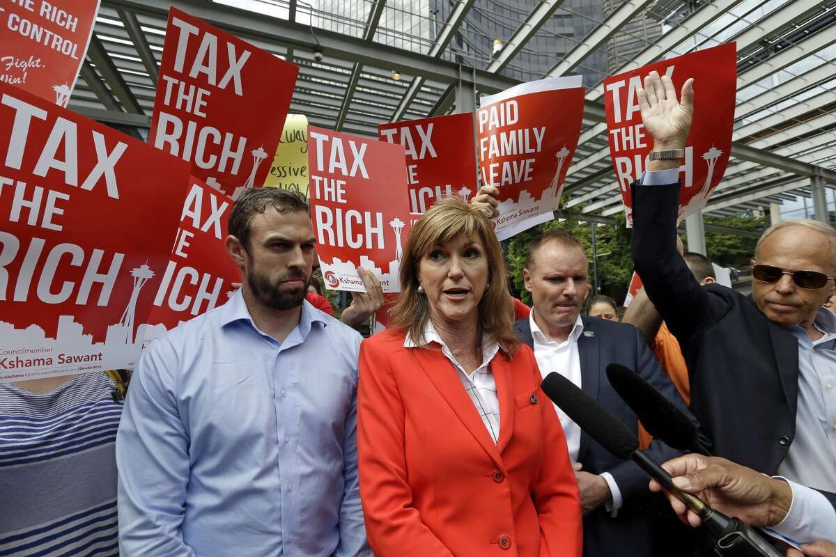 Then-Republican State Chairman Susan Hutchison, center, speaks with media members against a new city income tax on the wealthy as it ws approved by the Seattle City Council She was accompanied by party executive director (now Chairman) Caleb Heimlich. (AP Photo/Elaine Thompson)