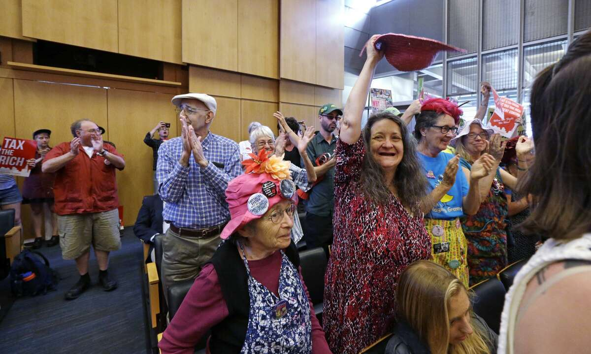 Audience members cheer in support at a Seattle City Council meeting as the council approves a new city income tax on the wealthy Monday, July 10, 2017, in Seattle. Seattle's wealthiest will become the only Washington state residents to pay an income tax under legislation unanimously approved by the City Council, a measure designed as much to raise revenue as to open a broader discussion about whether the wealthy pay their fair share. (AP Photo/Elaine Thompson)