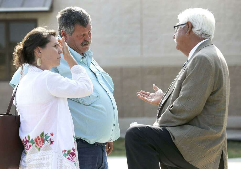 Defense attorney Rogelio Munoz (right) speaks Wednesday August 9, 2017 with Ben Young (left, center with mustache) outside of the Uvalde County Justice Center. Ben Young, according to Munoz, is the father of Jack Dillon Young, who has been charged with 13 two-count indictments alleging intoxication manslaughter and manslaughter, after being involved in a fatal bus crash in March 2016 in Leakey, Texas. A bond hearing for Jack Young has been reset for August 24, 2017, the same day as his arraignment. Photo: John Davenport, STAFF / San Antonio Express-News / ©John Davenport/San Antonio Express-News