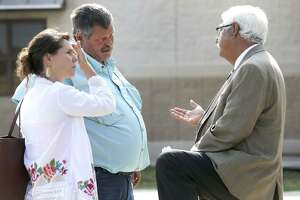 Defense attorney Rogelio Munoz (right) speaks Wednesday August 9, 2017 with Ben Young (left, center with mustache) outside of the Uvalde County Justice Center. Ben Young, according to Munoz, is the father of Jack Dillon Young, who has been charged with 13 two-count indictments alleging intoxication manslaughter and manslaughter, after being involved in a fatal bus crash in March 2016 in Leakey, Texas. A bond hearing for Jack Young has been reset for August 24, 2017, the same day as his arraignment.