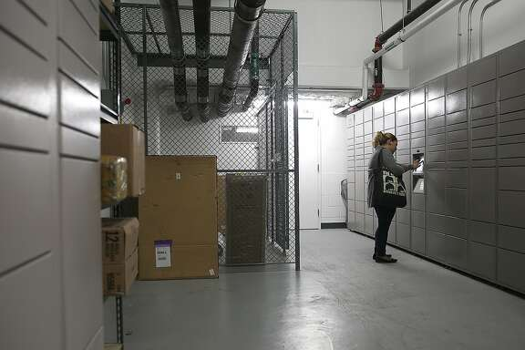 Katie Petrosyan puts a code in the Hub computer to receive her package of books on Wednesday, August 9, 2017, in San Francisco, Calif..  Amazon started Hub, a service where residents of apartment buildings receive packages in on-site lockers.