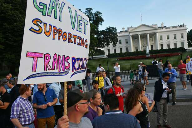 (FILES) This file photo taken on July 26, 2017 shows protesters gathering in front of the White House in Washington, DC. Five transgender women in the US military are suing President Donald Trump and the Pentagon over Trump's recent announcement he would reinstate a ban on transgender people serving in uniform. In a lawsuit filed in federal court August 9, 2017, the five plaintiffs from the Air Force, Coast Guard and the Army said they faced uncertainty about their futures, including whether they would be fired or lose post-military and retirement benefits. In a series of three tweets last month, Trump upended an Obama-era policy of more than a year that allowed transgender troops to serve openly.  / AFP PHOTO / PAUL J. RICHARDSPAUL J. RICHARDS/AFP/Getty Images