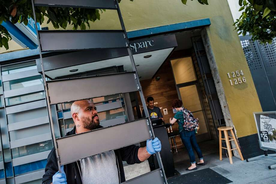 Luis Arturo Samayoa attaches security bars to the windows of the Sparc cannabis dispensary on Mission Street. Photo: Nick Otto, Special To The Chronicle