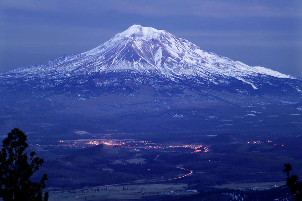 Mount Shasta looming over the town of Weed in the evening.