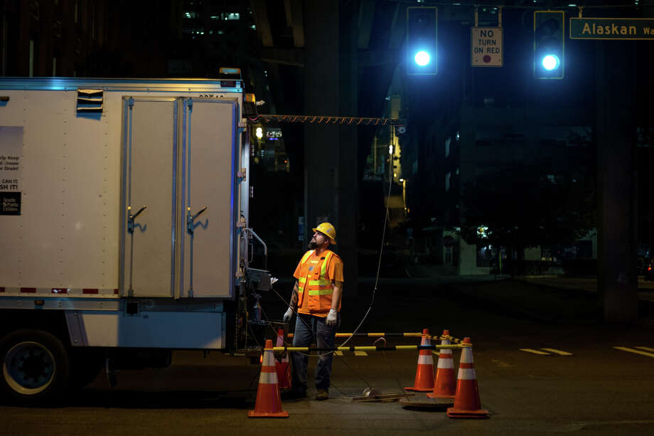 A sewer worker helps coworkers below the surface of Alaskan Way at 12:12 a.m. on Wednesday, Aug. 9, 2017. Photo: GRANT HINDSLEY, SEATTLEPI.COM / SEATTLEPI.COM