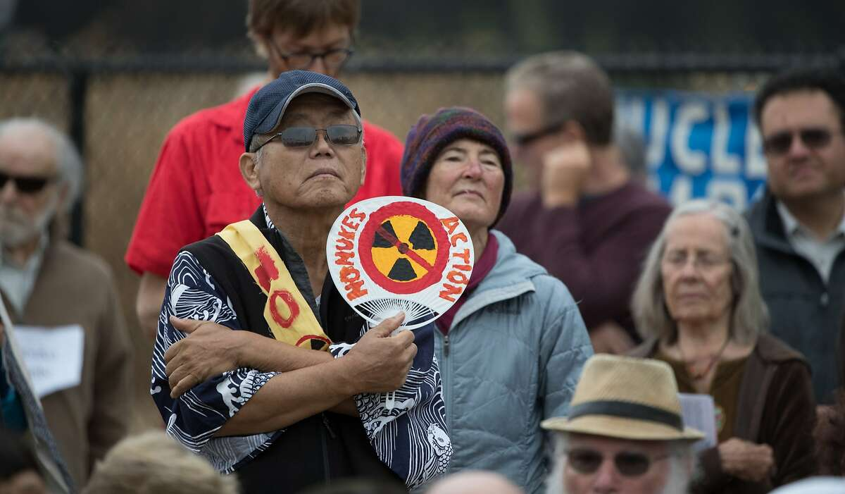 Sam Kano holds a sign at the annual observance of the A-bomb attack on Japan outside the fence of the Lawrence Livermore National Laboratory on Wednesday, Aug. 9, 2017 in Livermore, CA.