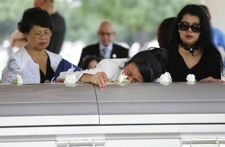 Virginia Axibal (center) and her sisters Carmelita Haverly (left) and Myrna Soriano mourn for their father, Dominador Soriano, 101, during a service at Fort Sam Houston National Cemetery.