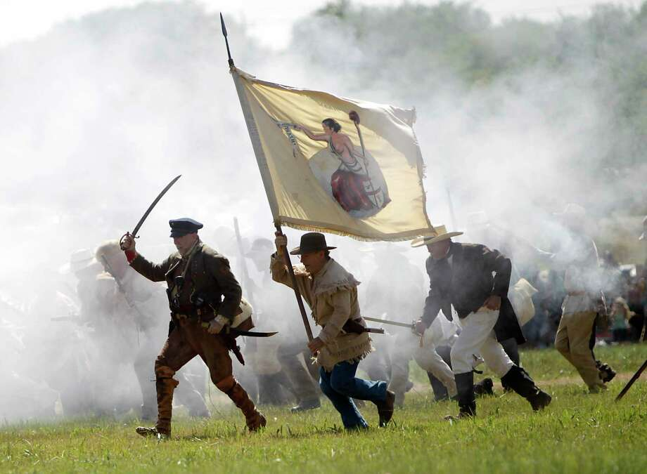 In this photo from April 16, 2011, the 175th anniversary of Texas' independence, re-enactors playing the parts of members of the Texian Army, charge toward the Mexican encampment during the Battle of San Jacinto on the grounds of the San Jacinto Battleground in Houston. ( Karen Warren / Houston Chronicle ) Photo: Karen Warren, Staff / © 2011 Houston Chronicle