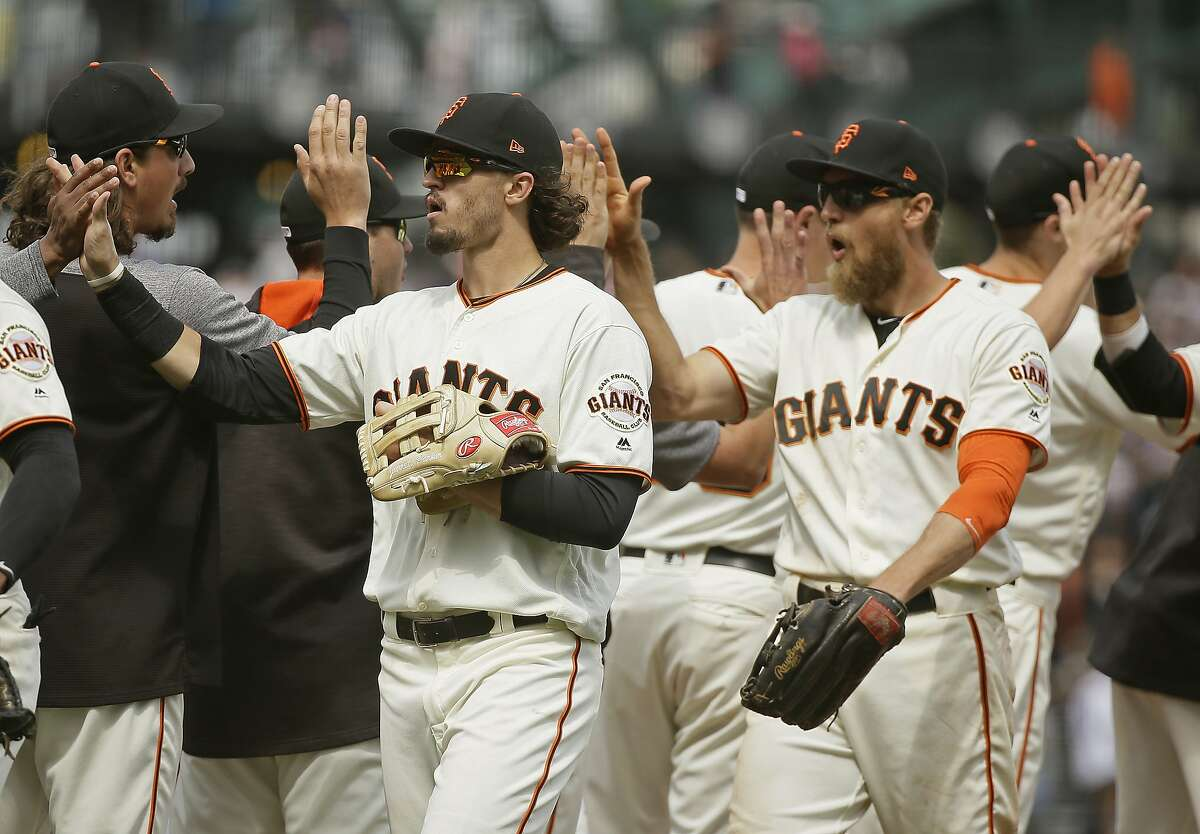 San Francisco Giants' Jarrett Parker, left, and Hunter Pence, right, are greeted at the end of a baseball game against the Chicago Cubs Wednesday, Aug. 9, 2017, in San Francisco. San Francisco won the game 3-1.