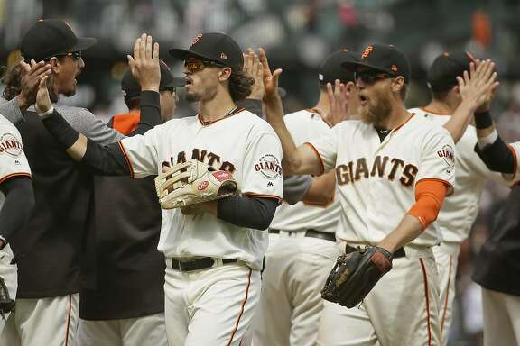 San Francisco Giants' Jarrett Parker, left, and Hunter Pence, right, are greeted at the end of a baseball game against the Chicago Cubs Wednesday, Aug. 9, 2017, in San Francisco. San Francisco won the game 3-1. (AP Photo/Eric Risberg)