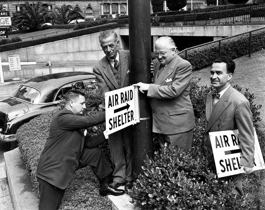 George Galvin, Admiral A.G. Cook, Mayor Elmer Robinson and Andrew Pansini set up air raid signs before a civil defense drill in San Francisco's Union Square on June 19, 1951. Photo: Bob Campbell, The Chronicle