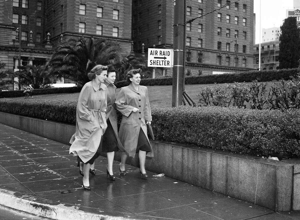 Three women walk toward the Union Square garage during an air raid drill in San Francisco on March 11, 1952.