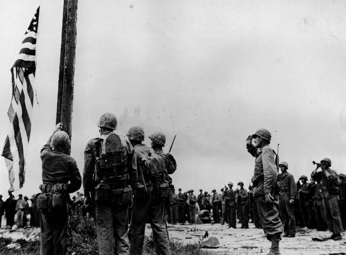 June 3, 1944: The American flag 'Old Glory' is raised on Guam for the first time in two and a half years, it was occupied from 1941 by the Japanese. Col Merlin F Schneider, the commanding officer of the Marines that recaptured the area, salutes the flag.