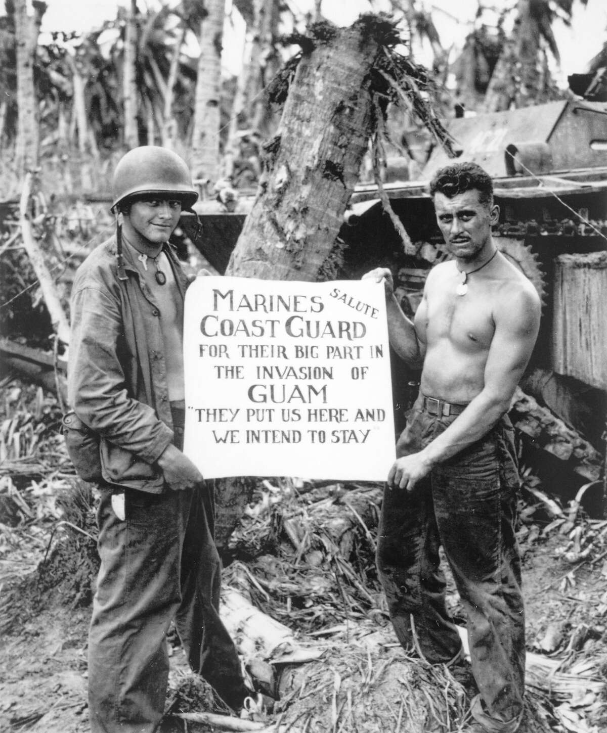 """Two U.S. Marines hold up a sign saluting the efforts of the U.S. Coast Guard during the Second Battle of Guam, August 1944. The sign reads """"Marines Salute Coast Guard for their Big Part in the Invasion of Guam - they put us here and we intend to stay."""""""