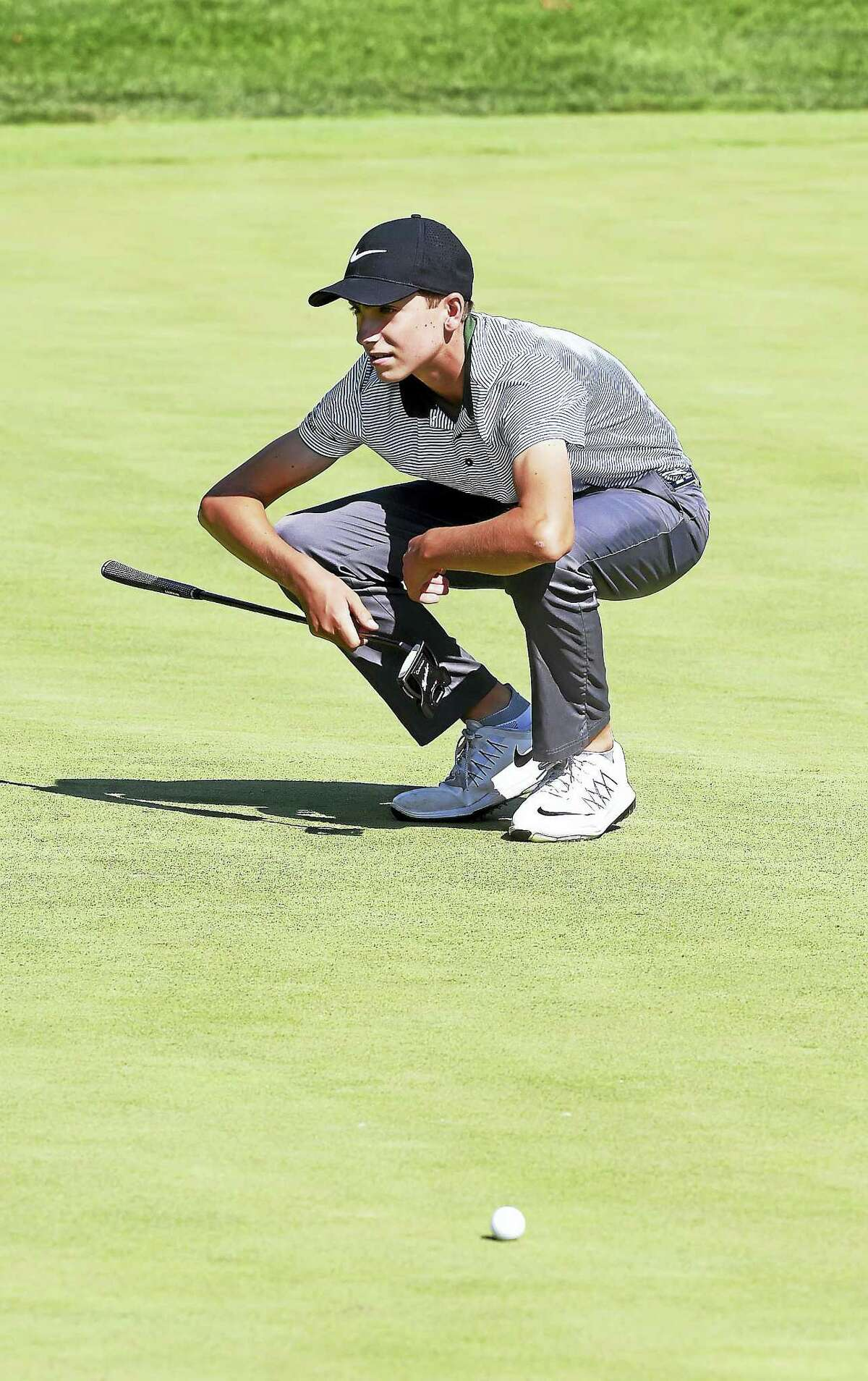Ben James of Milford lines up a putt on the ninth hole of the 16th Northern Junior Championship.