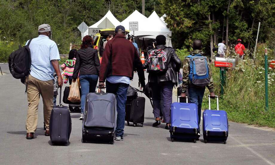 A family from Haiti approach a tent in Saint-Bernard-de-Lacolle, Quebec, stationed by Royal Canadian Mounted Police, as they haul their luggage down Roxham Road in Champlain, N.Y., Monday, Aug. 7, 2017. Officials on both sides of the border first began to notice last fall, around the time of the U.S. presidential election, that more people were crossing at Roxham Road. Since then the numbers have continued to climb. (AP Photo/Charles Krupa) ORG XMIT: NYCK106 Photo: Charles Krupa / Copyright 2017 The Associated Press. All rights reserved.
