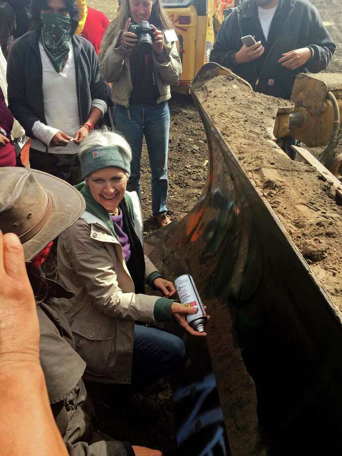 """FILE - In this Sept. 6, 2016, file photo, Green Party presidential candidate Jill Stein prepares to spray-paint """"I approve this message"""" in red paint on the blade of a bulldozer at a protest against the Dakota Access Pipeline in the area of Morton County, N.D. Stein has reached a plea agreement with prosecutors to resolve criminal charges filed against her in North Dakota nearly a year ago for protesting the Dakota Access oil pipeline, court records show. (Alicia Ewen/KX News via AP, File) Photo: TEL / KX News"""