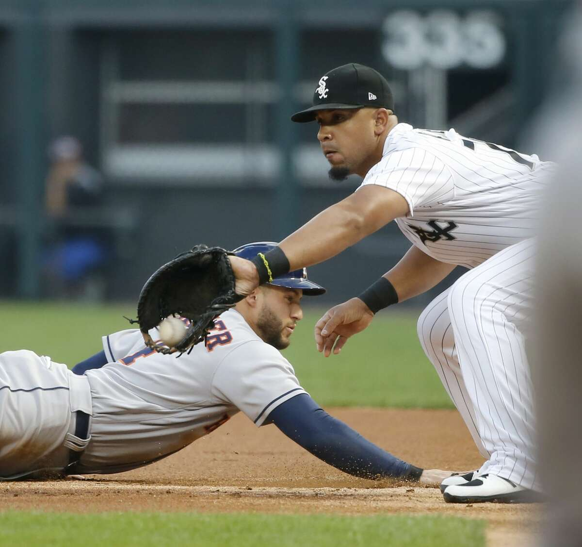 Houston Astros' George Springer, left, dives safely back to first on a pick off attempt by Chicago White Sox starting pitcher Miguel Gonzalez to first baseman Jose Abreu during the first inning of a baseball game Wednesday, Aug. 9, 2017, in Chicago. (AP Photo/Charles Rex Arbogast)