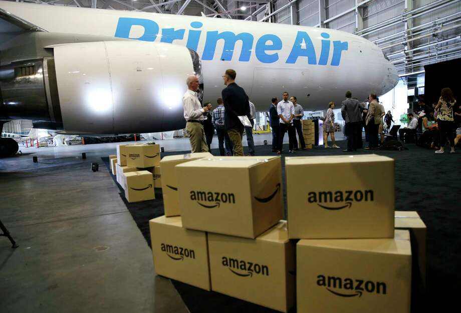 "FILE - In this Aug. 4, 2016 file photo, Amazon.com boxes are shown stacked near a Boeing 767 Amazon ""Prime Air"" cargo plane on display in a Boeing hangar in Seattle. Buffeted by threats from Amazon drones and Uber to delivery by golf cart, the beleaguered U.S. Postal Service is counting on a different strategy to stay ahead in the increasingly competitive package business: more freedom to raise your letter prices.  (AP Photo/Ted S. Warren, File) Photo: Ted S. Warren, STF / Copyright 2016 The Associated Press. All rights reserved. This material may not be published, broadcast, rewritten or redistribu"