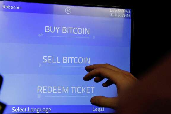 FILE - In this Thursday, March 20, 2014, file photo, Christopher David uses a Robocoin kiosk to sell bitcoins outside of the 500 Startups' Bitcoinference in Mountain View, Calif. Bitcoin, the digital currency, is the payment of choice for HBO's cyberattackers. Bitcoin allows people to buy goods and services and exchange money without involving banks, credit card issuers or other third parties. It remains relatively little used, but holds big appeal for tech enthusiasts, speculators and criminals. (AP Photo/Jeff Chiu, File)