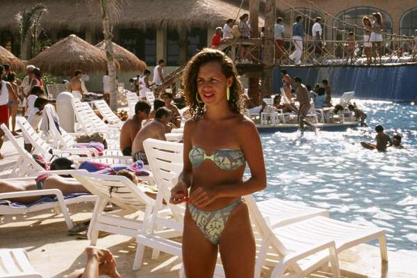1989:  A woman in a bikini poses next to a resort pool in this Quintana Roo, Mexico, photo.
