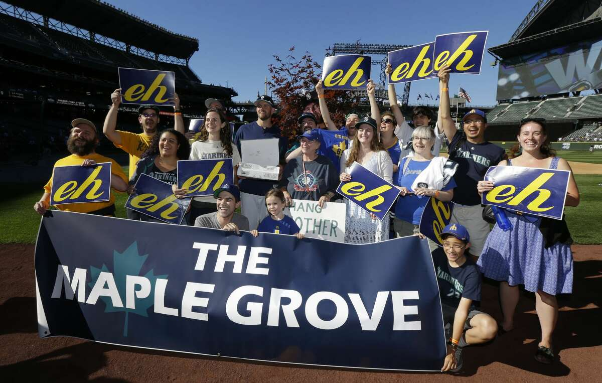 """Seattle Mariners pitcher James """"The Big Maple"""" Paxton, center, poses for a photo with fans who helped create the """"Maple Grove"""" cheering section in the left field bleachers at Safeco Field, Tuesday, July 25, 2017, before the Mariners' baseball game against the Boston Red Sox in Seattle. The section, which cheered Paxton on Monday in the Mariners' 4-0 win over the Red Sox, features a maple tree with Paxton's photo in the leaves and fans who wave signs and chant """"Eh!"""" in reference to Paxton's home country of Canada instead of the shouts of """"K"""" for strikeouts by Felix Hernandez. (AP Photo/Ted S. Warren)"""