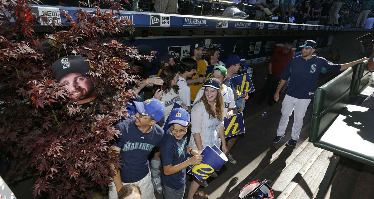 """Seattle Mariners pitcher James """"The Big Maple"""" Paxton, right, visits in the dugout with fans who helped create the """"Maple Grove"""" cheering section in the left field bleachers at Safeco Field, Tuesday, July 25, 2017, before the Mariners' baseball game against the Boston Red Sox in Seattle. (AP Photo/Ted S. Warren)"""