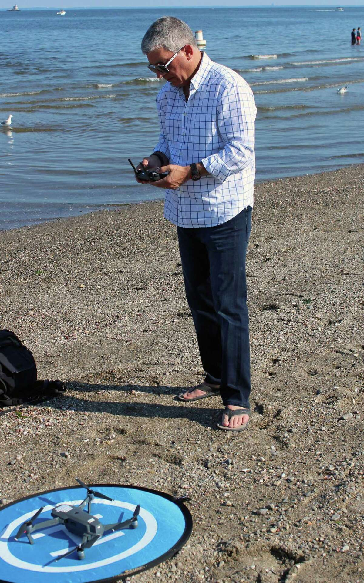 Photographer Stephen Wilkes prepares to take some drone footage as he scouts the location for his day-to- night photo project at Jennings Beach.