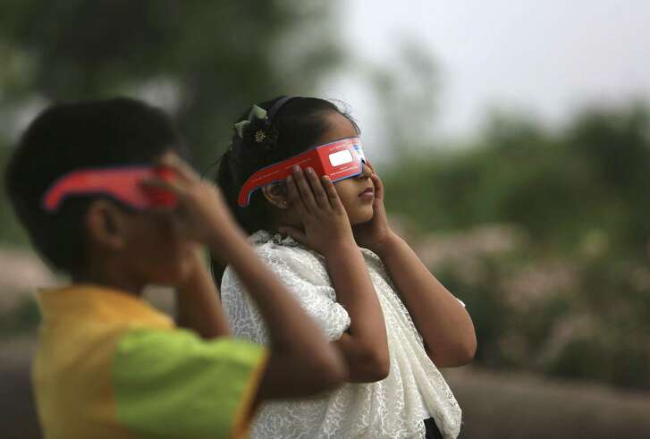 The safest way to directly view an eclipse is through special-purpose solar eclipse glasses that filter out harmful UV rays. Look for eclipse glasses that comply with the ISO 12312-2 international safety standard. Here children watch a partial solar eclipse in Hyderabad, India in 2016.