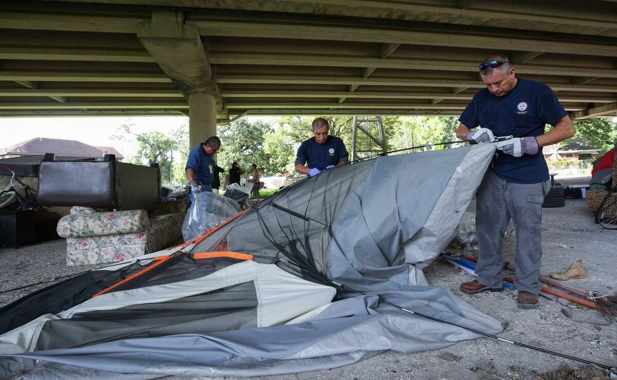 Miguel Mendoza, left to right, Robert Lam, and Alejandro Canton with the City of Houston General Service Department break down a tent that was left behind as officials evacuated a homeless encampment due to serious health hazards under the Highway 59 overpass, between Caroline and La Branch streets Thursday, Aug. 10, 2017, in Houston. People will be able to return once the city is done with cleanup of the area. ( Godofredo A. Vasquez / Houston Chronicle )