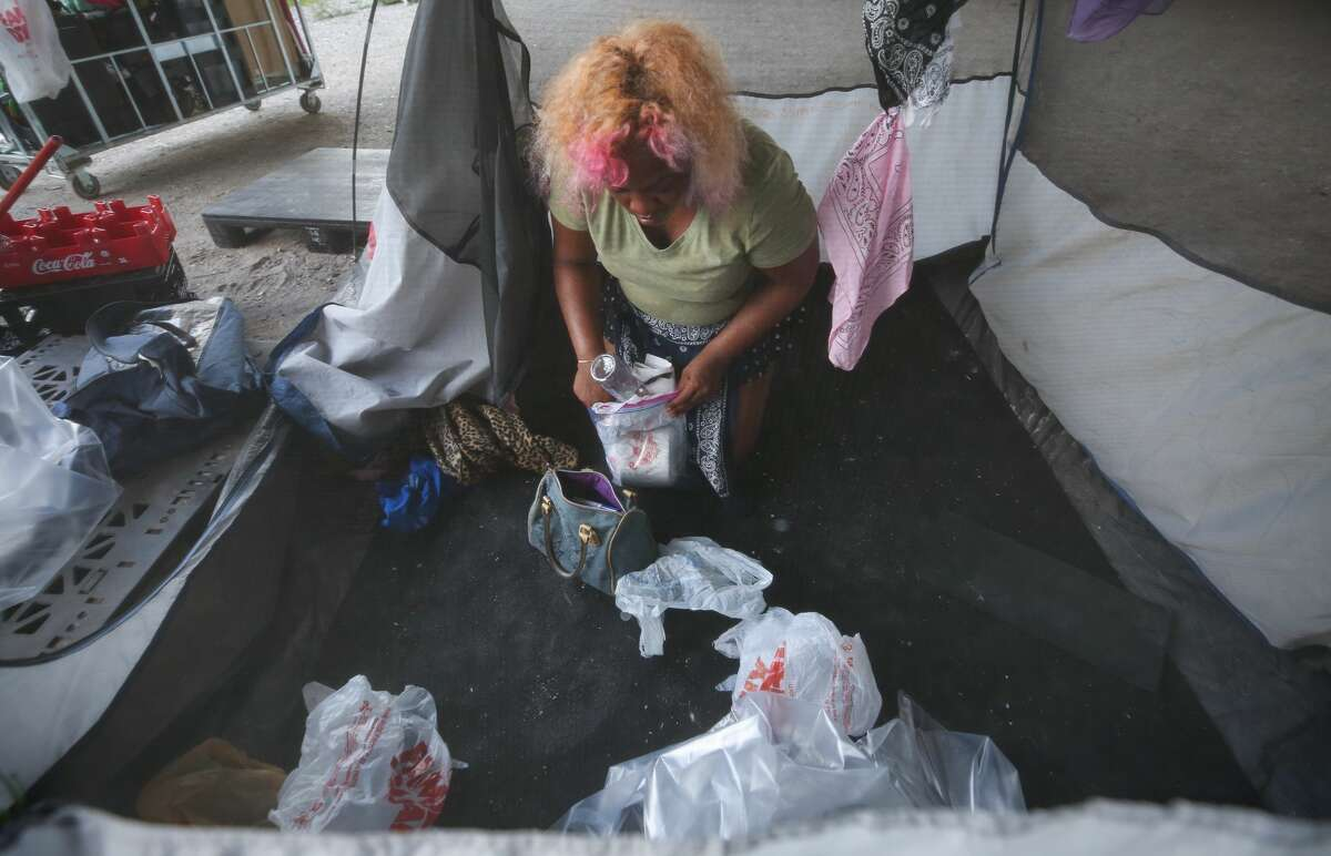 Bernadette Parker collects her belongings as city officials evacuated a homeless encampment due to serious health hazards under the Highway 59 overpass, between Caroline and La Branch streets Thursday, Aug. 10, 2017, in Houston. People will be able to return once the city is done with cleanup of the area. ( Godofredo A. Vasquez / Houston Chronicle )